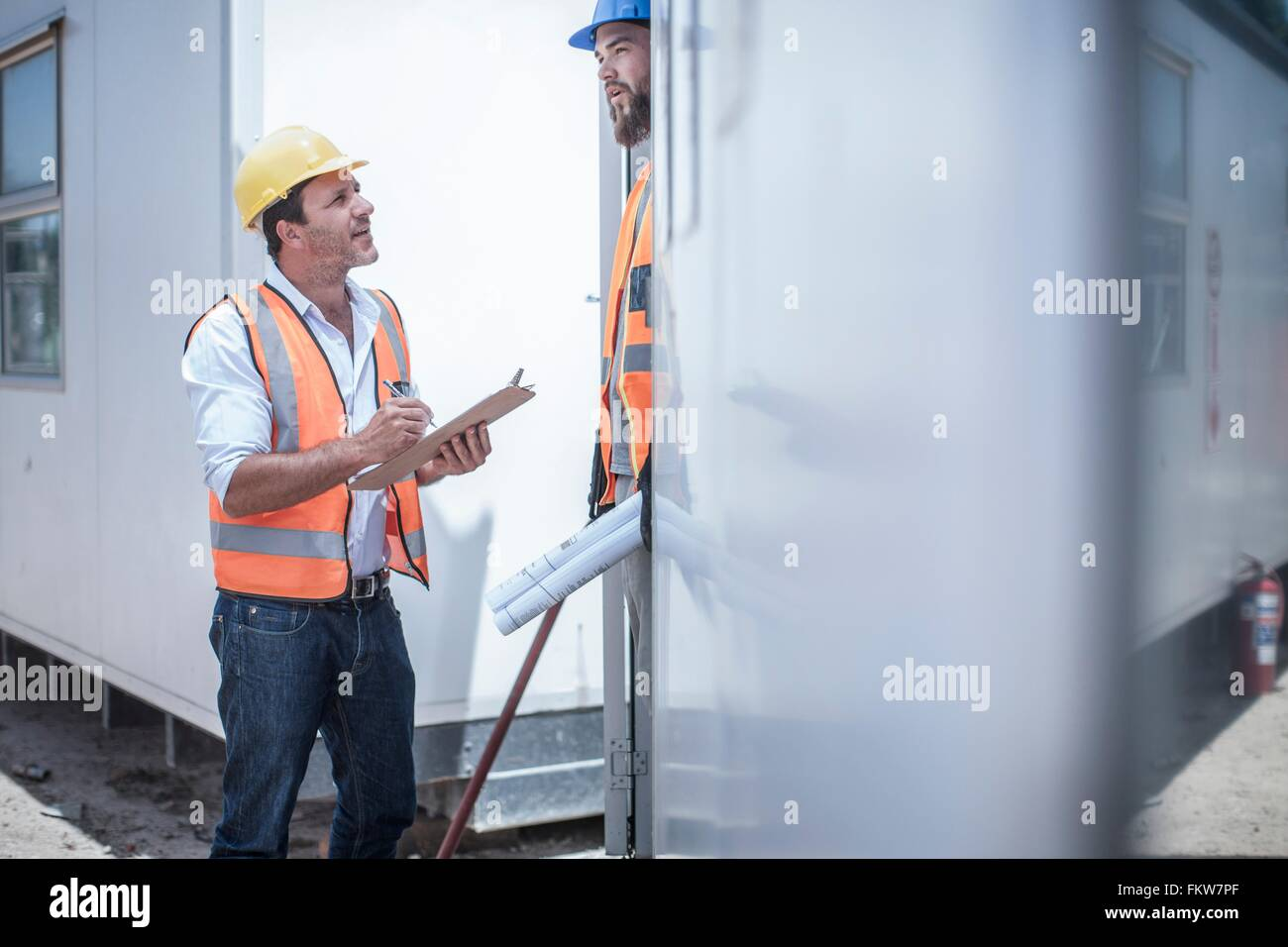 Construction worker talking to foreman from doorway of construction cabin - Stock Image