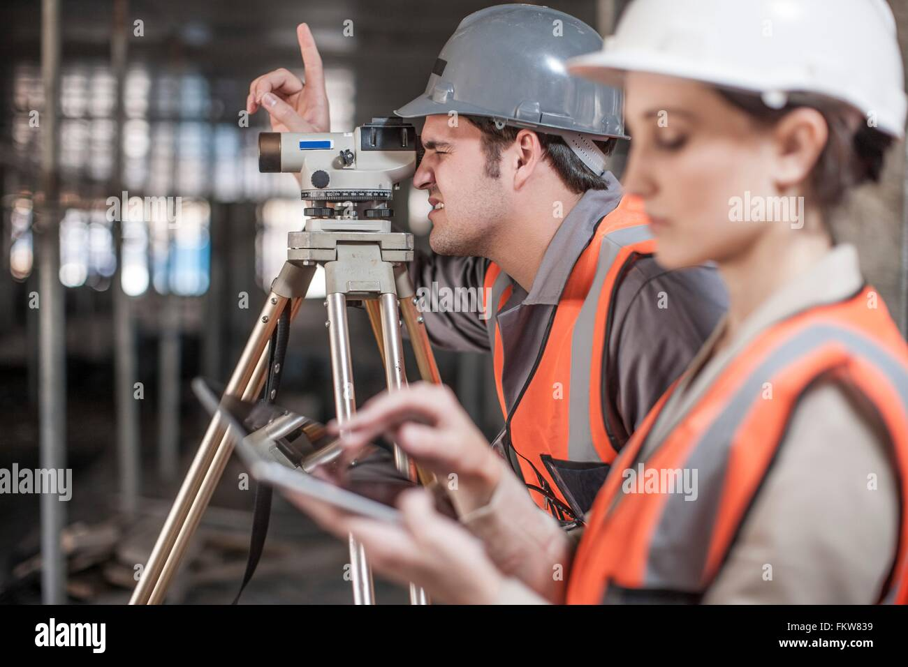 Female and male surveyor using digital tablet and theodolite  on construction site - Stock Image