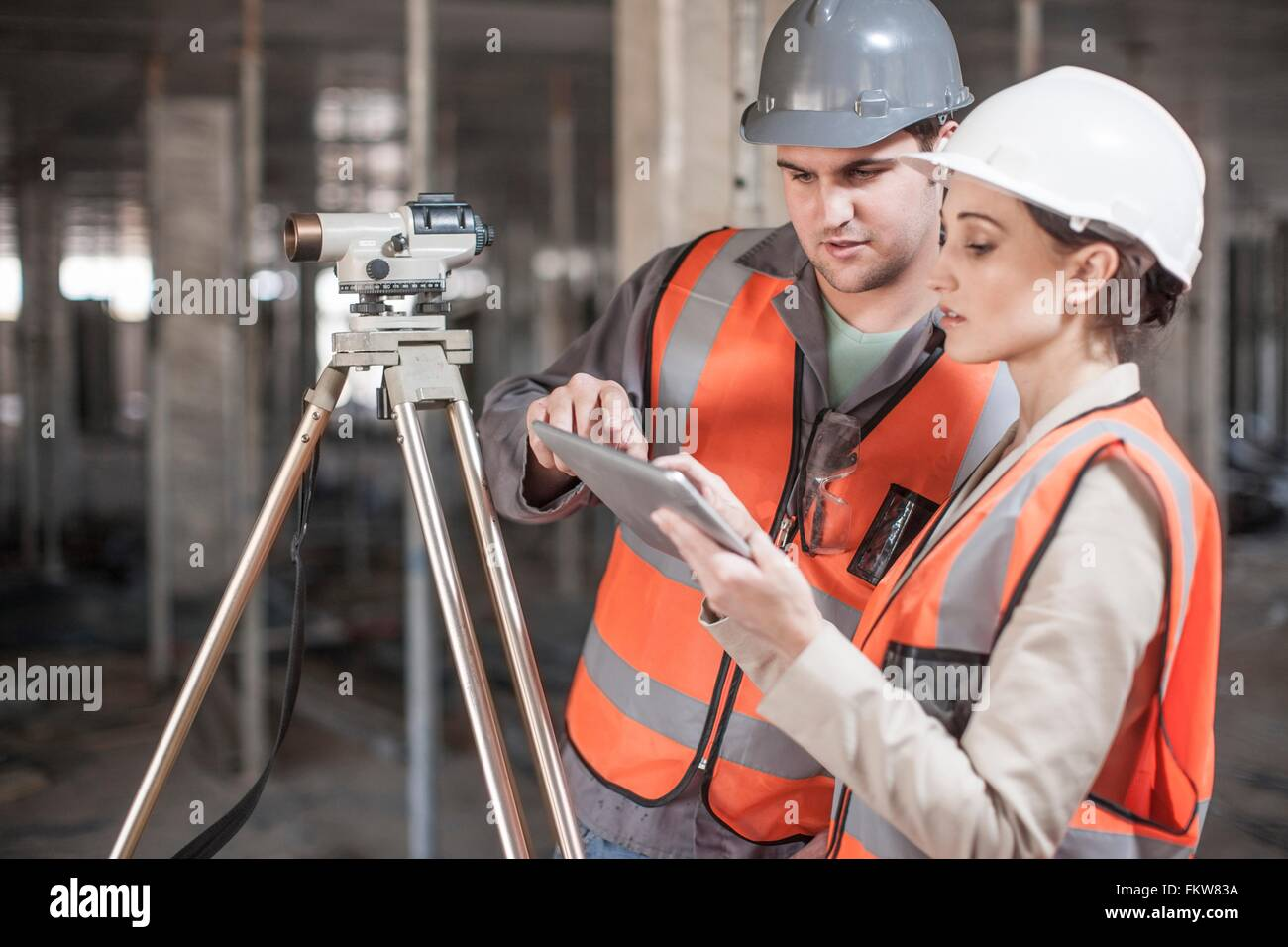 Female and male surveyor using digital tablet on construction site - Stock Image