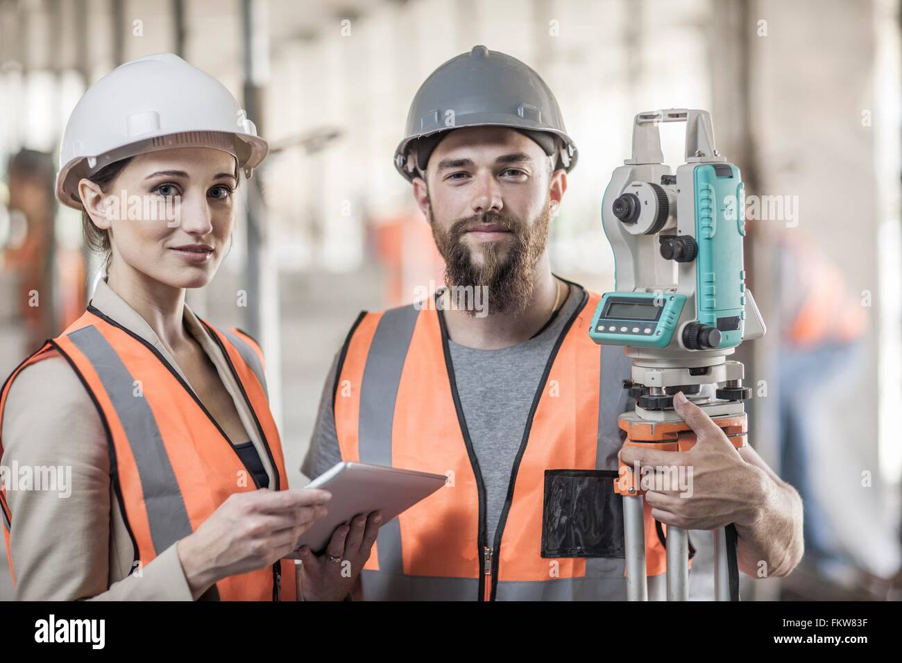 Portrait of young male and female surveyors on construction site - Stock Image
