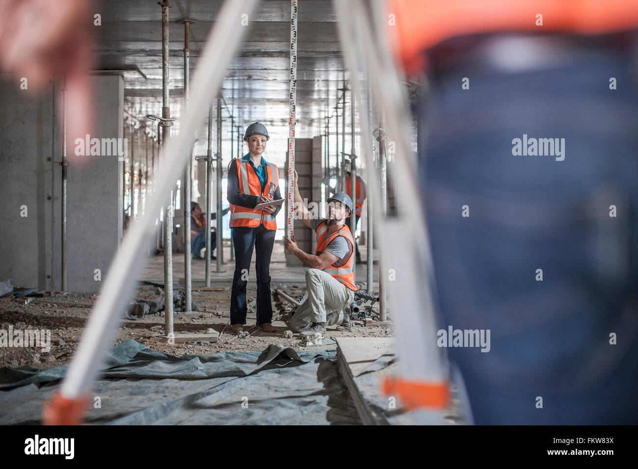 Male and female builders taking measurements for surveyor - Stock Image