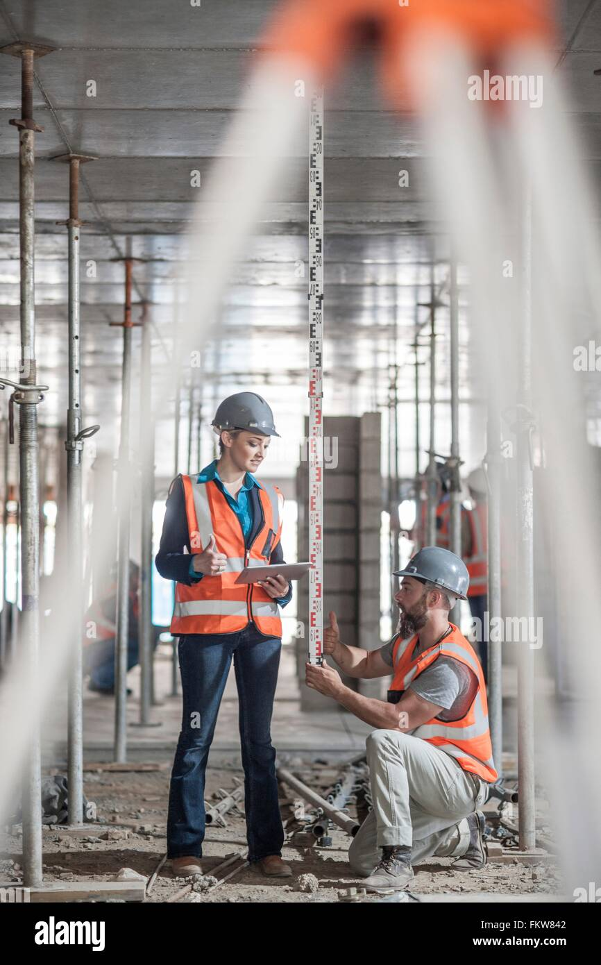 Male and female builders measuring construction with ruler - Stock Image