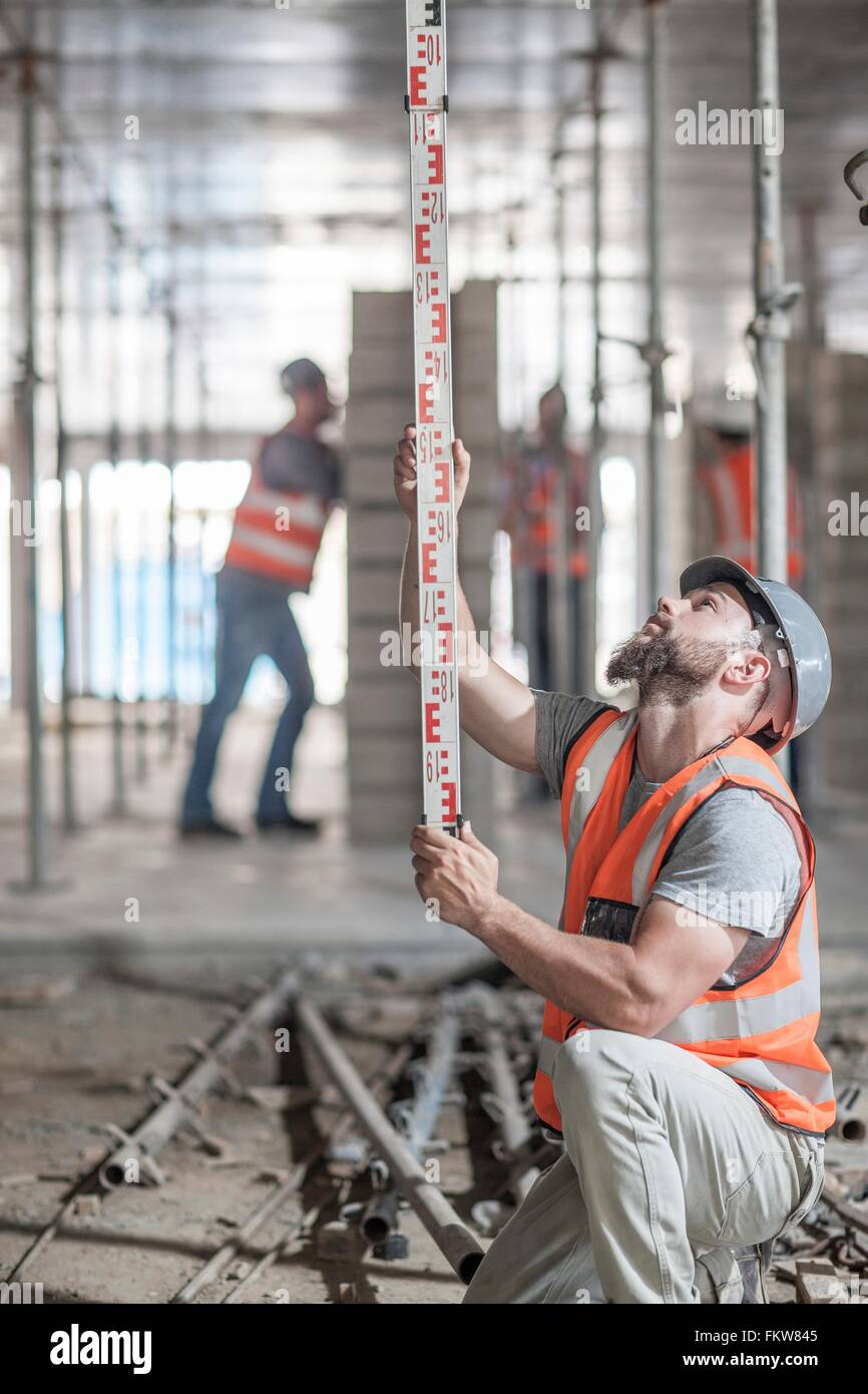 Young male builder measuring construction with ruler - Stock Image