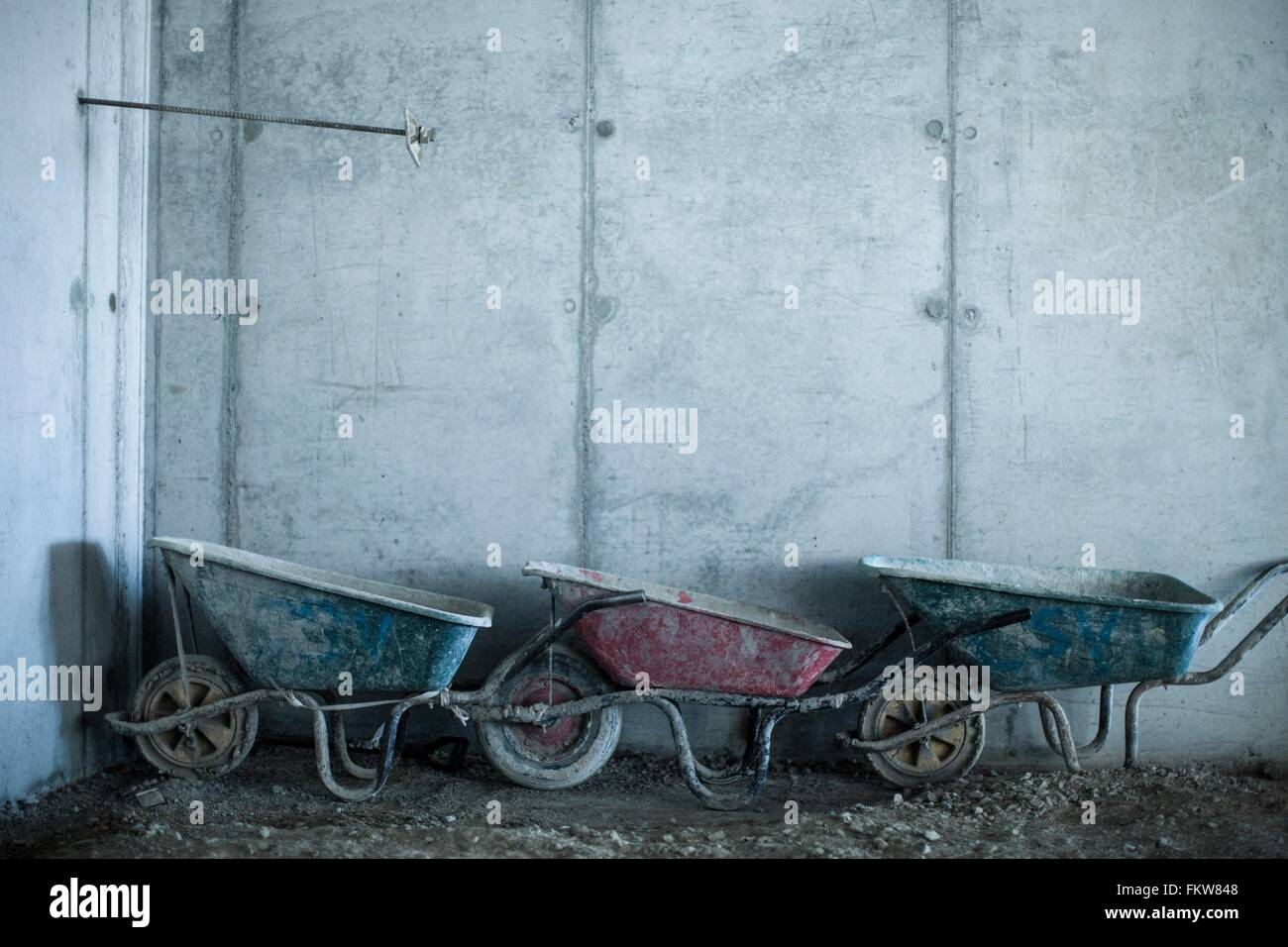 Row of three wheelbarrows on construction site - Stock Image