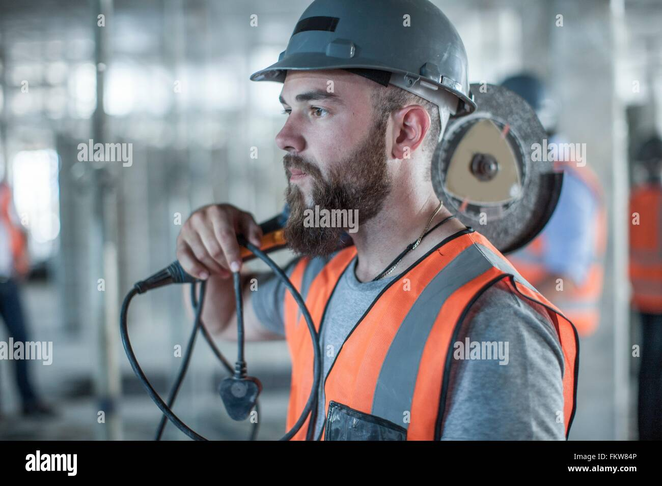 Young male builder carrying circular saw on shoulder on construction site - Stock Image