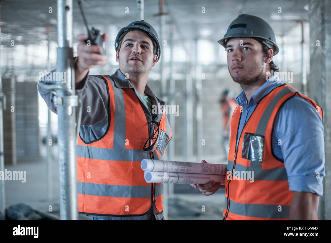 Site manager and builder pointing on construction site - Stock Image