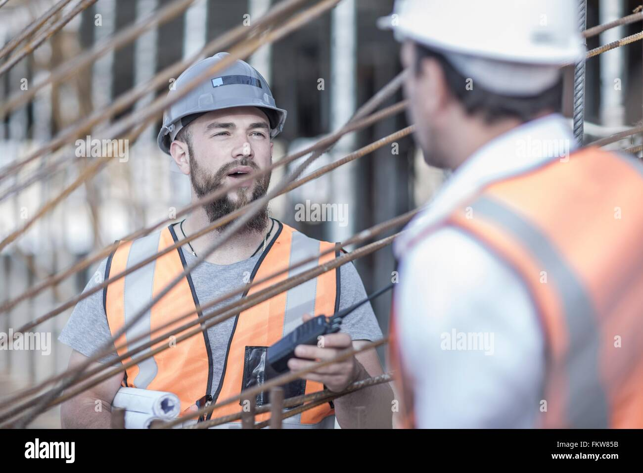 Site manager and builder discussing steel rods on  construction site - Stock Image