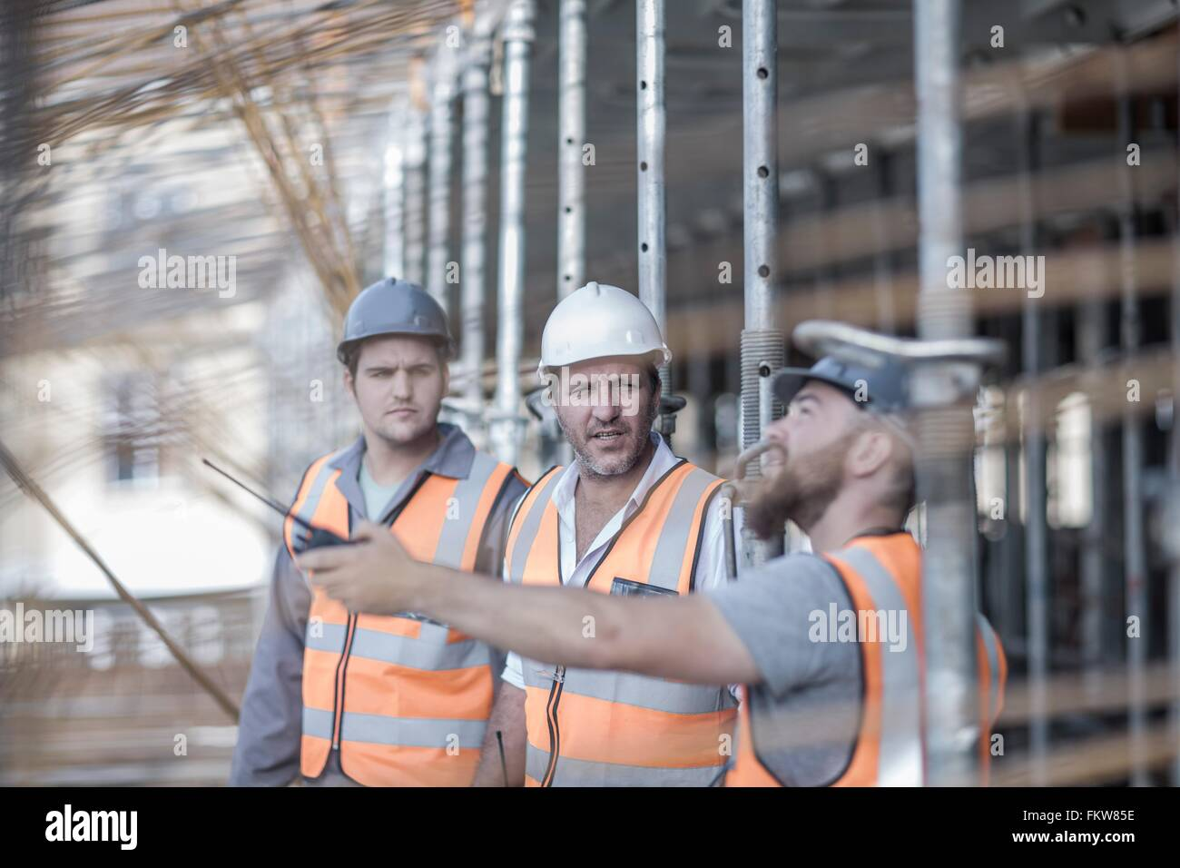 Site manager and builders pointing to steel rods on  construction site - Stock Image