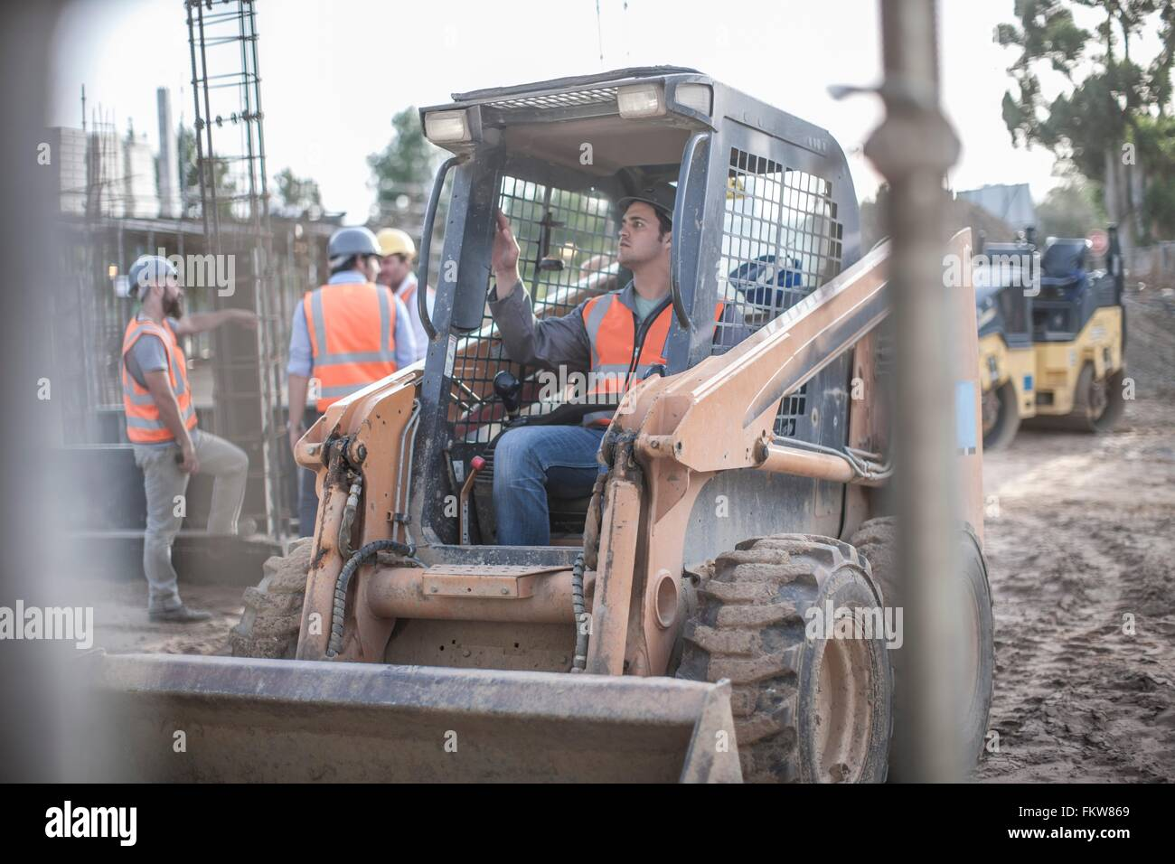Construction worker driving excavator on construction site - Stock Image