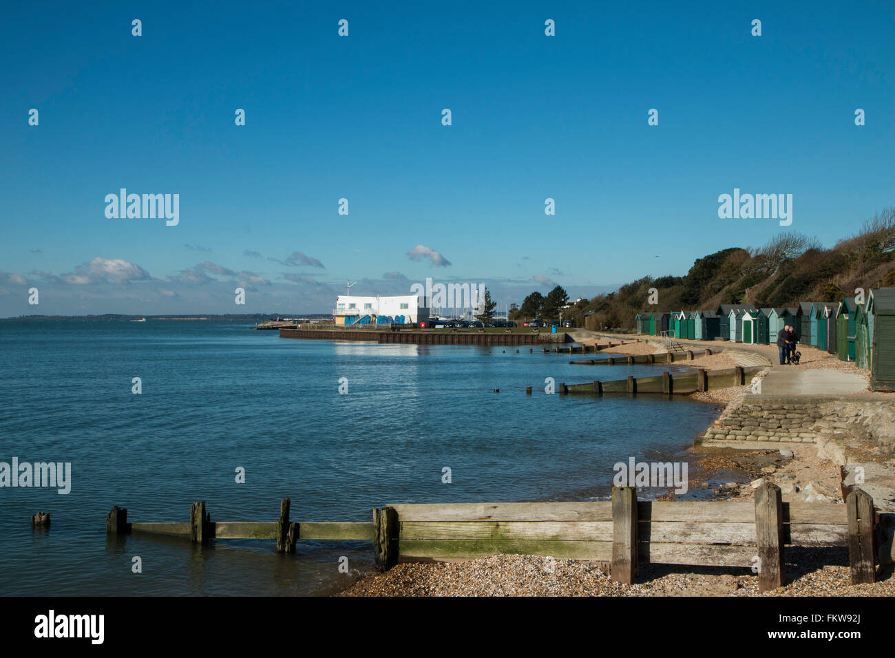 Meon Shore, Hampshire at full tide with Beach Huts to the right. Hillhead sailing club is in the distance - Stock Image