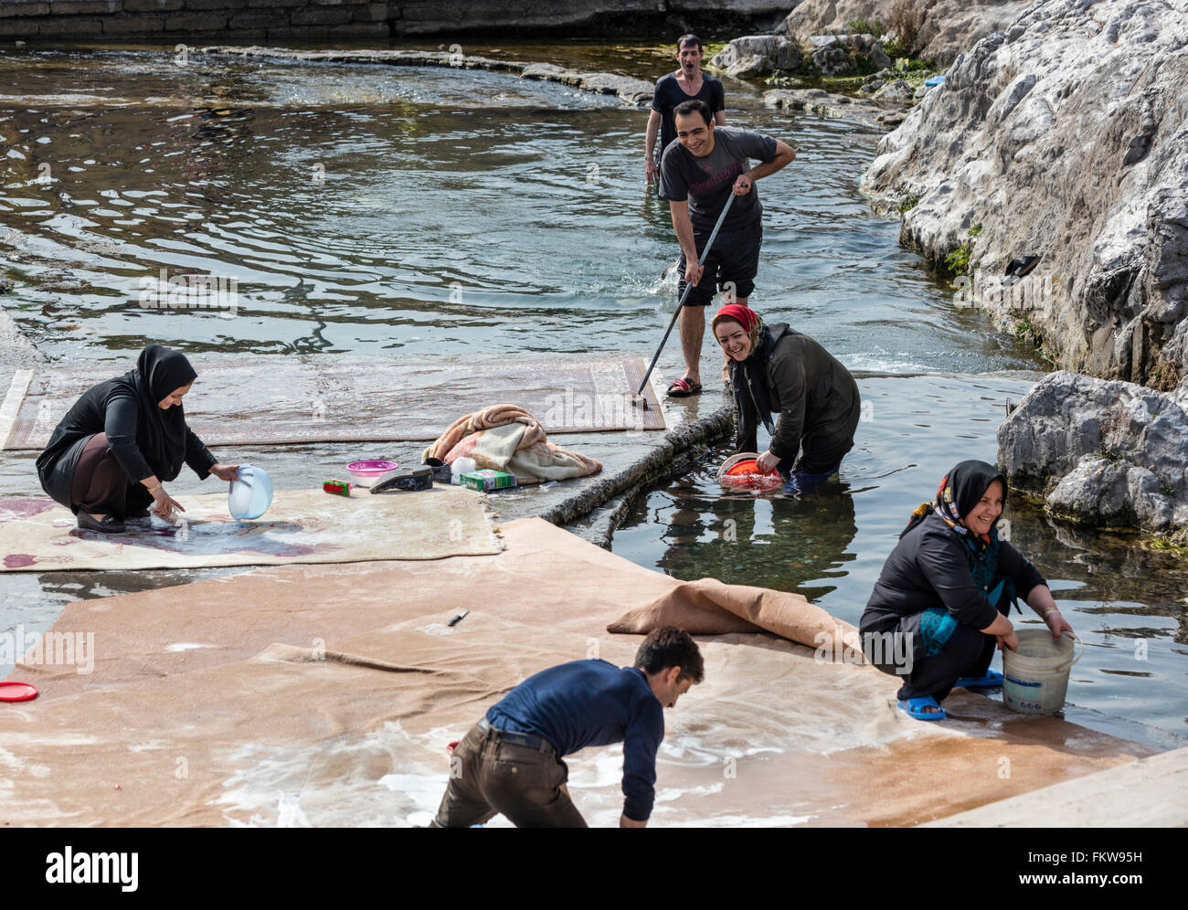 Traditional springtime carpet washing at the Cheshmeh Ali spring at Rayy in southern Tehran. - Stock Image