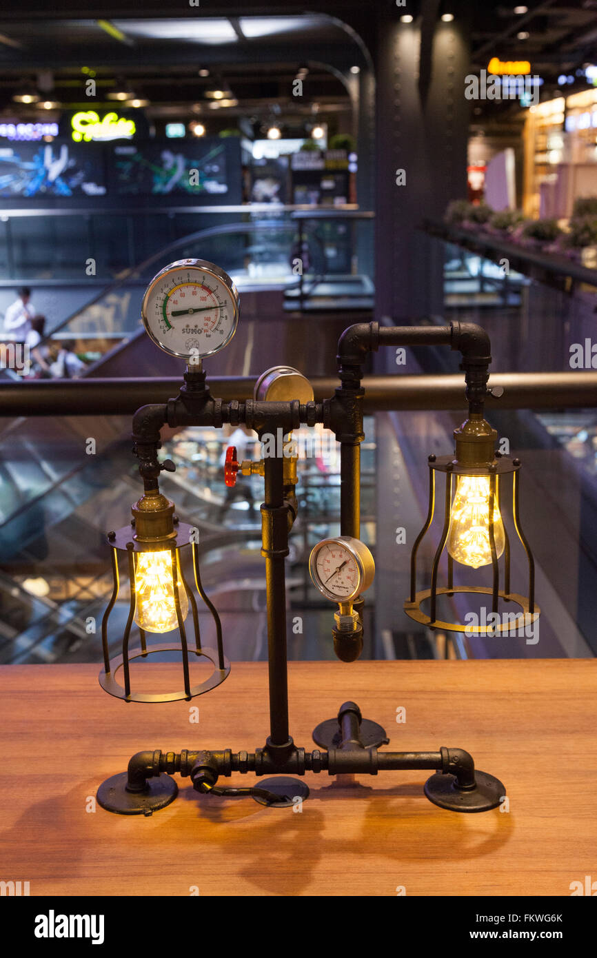 A very funny table lamp - with two bulbs, gauges and gate valve - on a stand made out of black industrial metal - Stock Image