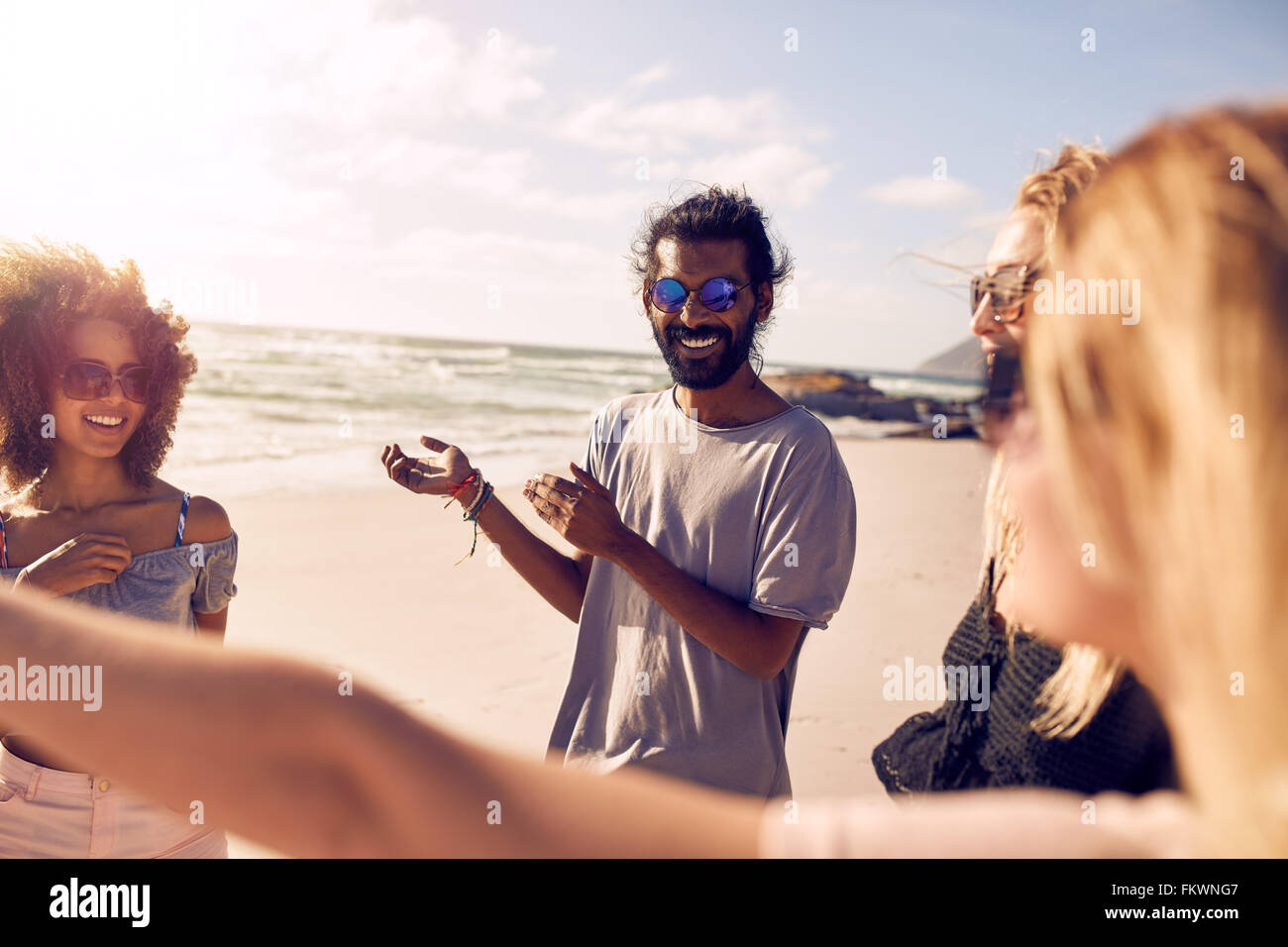 Diverse group of young people standing together and talking. Friends enjoying themselves on a sunny day at the beach. - Stock Image