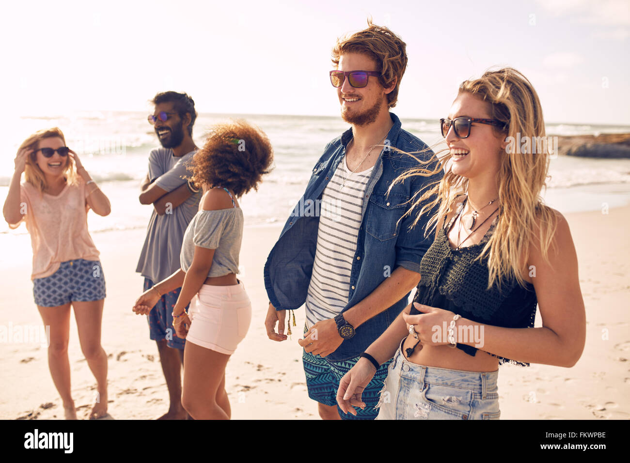 Group of friends walking along a beach at summertime. Happy young people enjoying a day at beach. - Stock Image