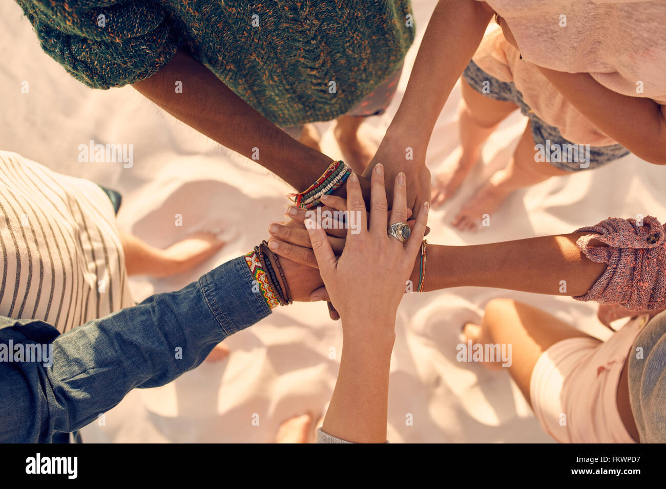 Group of young men and women showing unity. Group of young friends putting their hands together at the beach. - Stock Image