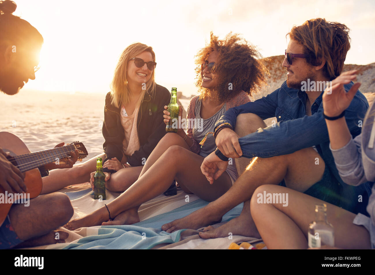 Portrait of group of young friends having a party on the beach in evening. Men and women drinking beers and listening - Stock Image