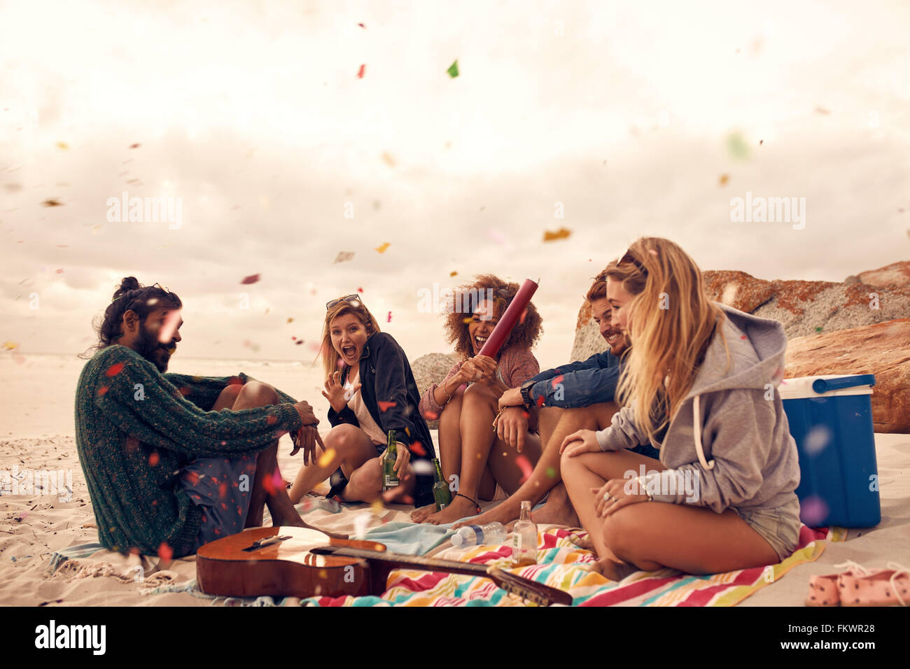 Happy friends partying on the beach with drinks and confetti. Happy young people having fun at beach party, celebrating - Stock Image