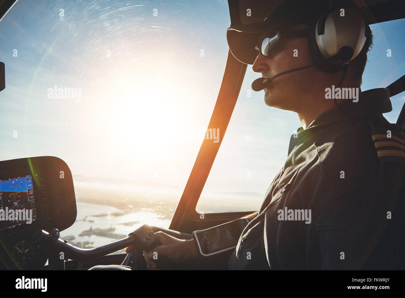 Close up of a pilot flying a helicopter with sun flare entering the cockpit. - Stock Image