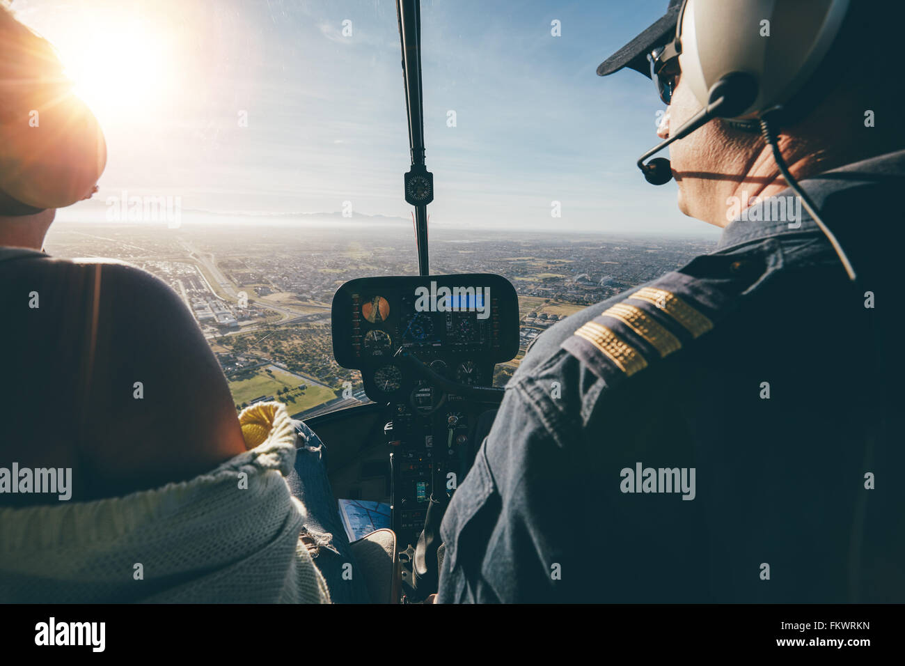 Rear view of two pilots flying a helicopter on sunny day. Close up shot of pilots sitting in the cockpit with bright - Stock Image