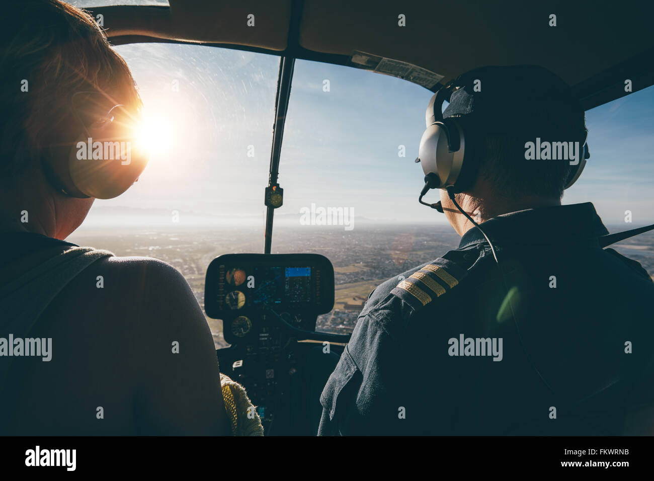 Two pilots in a helicopter while flying on a sunny day. rear view shot of man and woman pilots - Stock Image