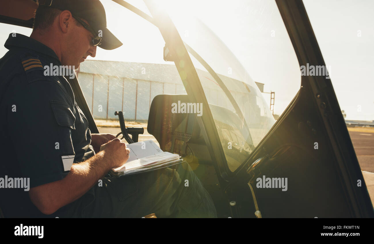 Helicopter pilot checking the flight manual before a take off. Helicopter is on the ground with bright sunlight. - Stock Image