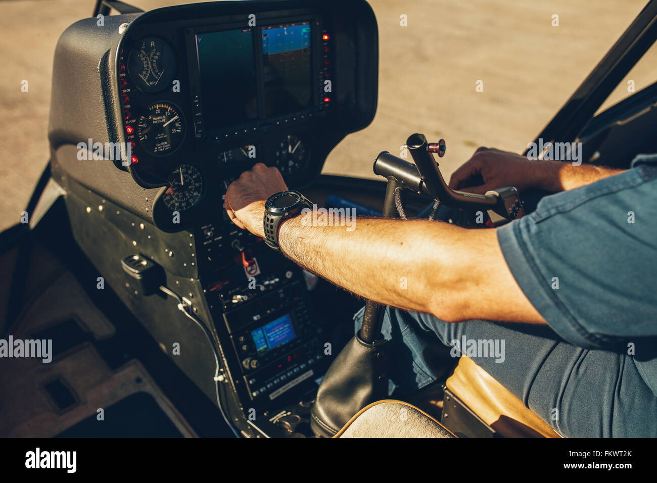 Close up shot of pilot checking the gauges on the instrument panel dashboard of  a helicopter. Pilot's hand - Stock Image