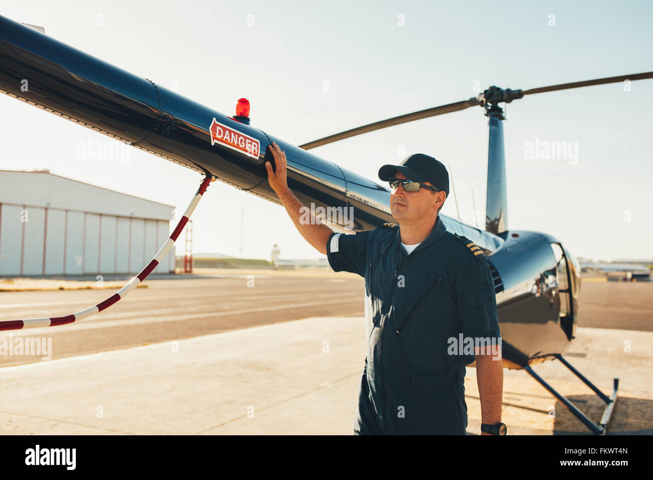Male pilot standing at the tail of a helicopter and looking away. Mechanic inspecting helicopter before take off. - Stock Image