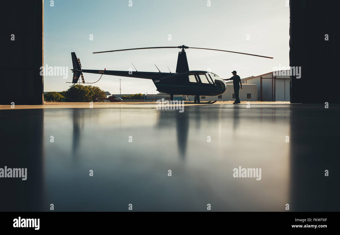 Silhouette of helicopter in the hangar with a pilot. Pilot doing preflight inspection of a helicopter. - Stock Image
