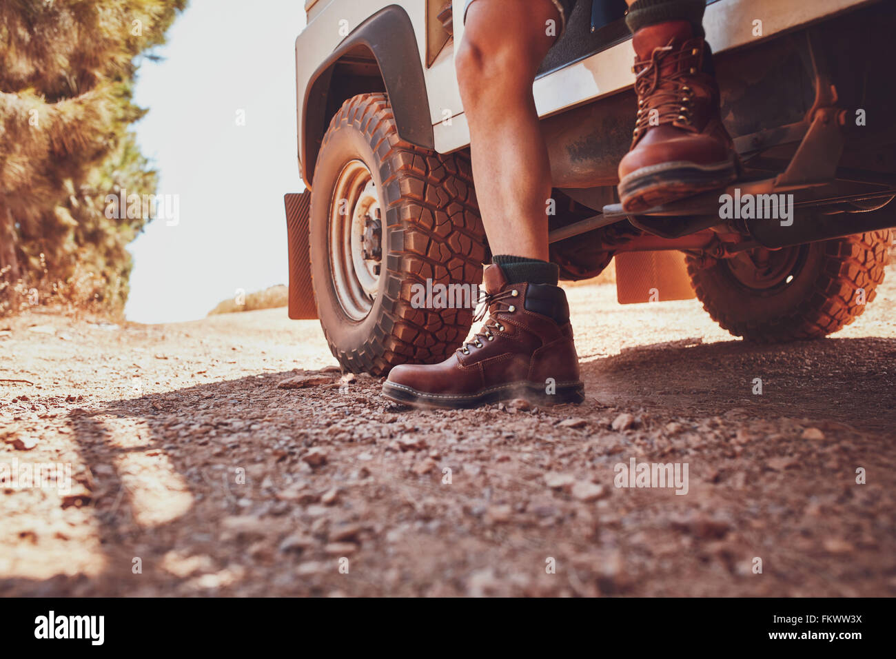 Close up of male leg with leather boot stepping out of a off road vehicle. Car parked on the dirt road in countryside. Stock Photo