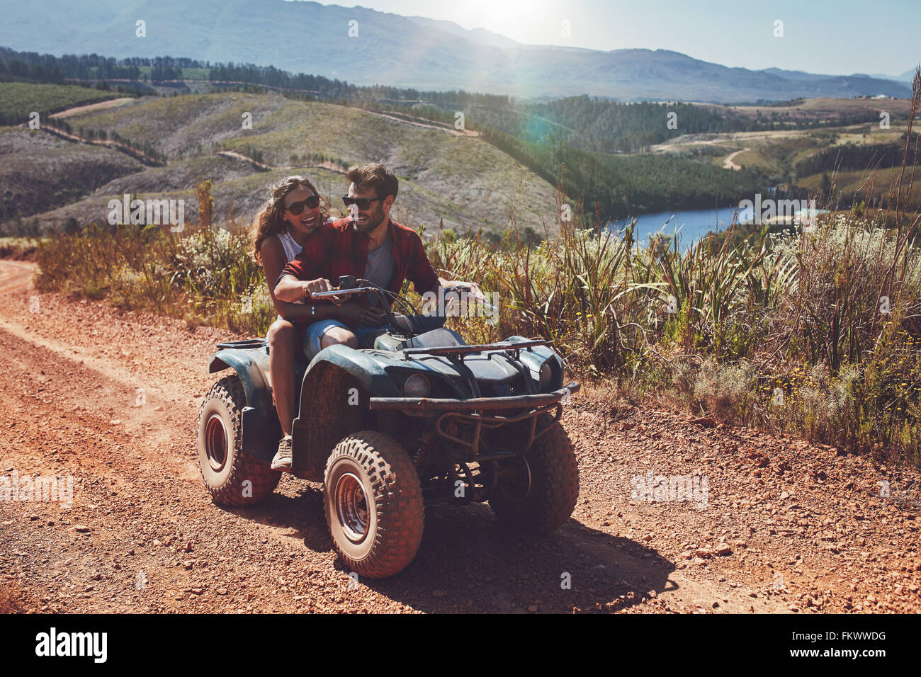 Young couple having fun on mountain while driving a quad bike on a summer day. Young man and woman on an ATV. - Stock Image