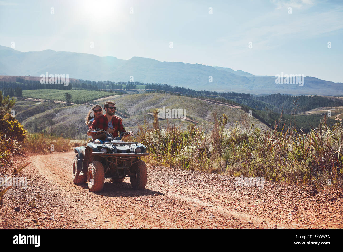 Young man and woman having fun while driving a quad bike. Young couple enjoying off road vehicle ride on a summer - Stock Image