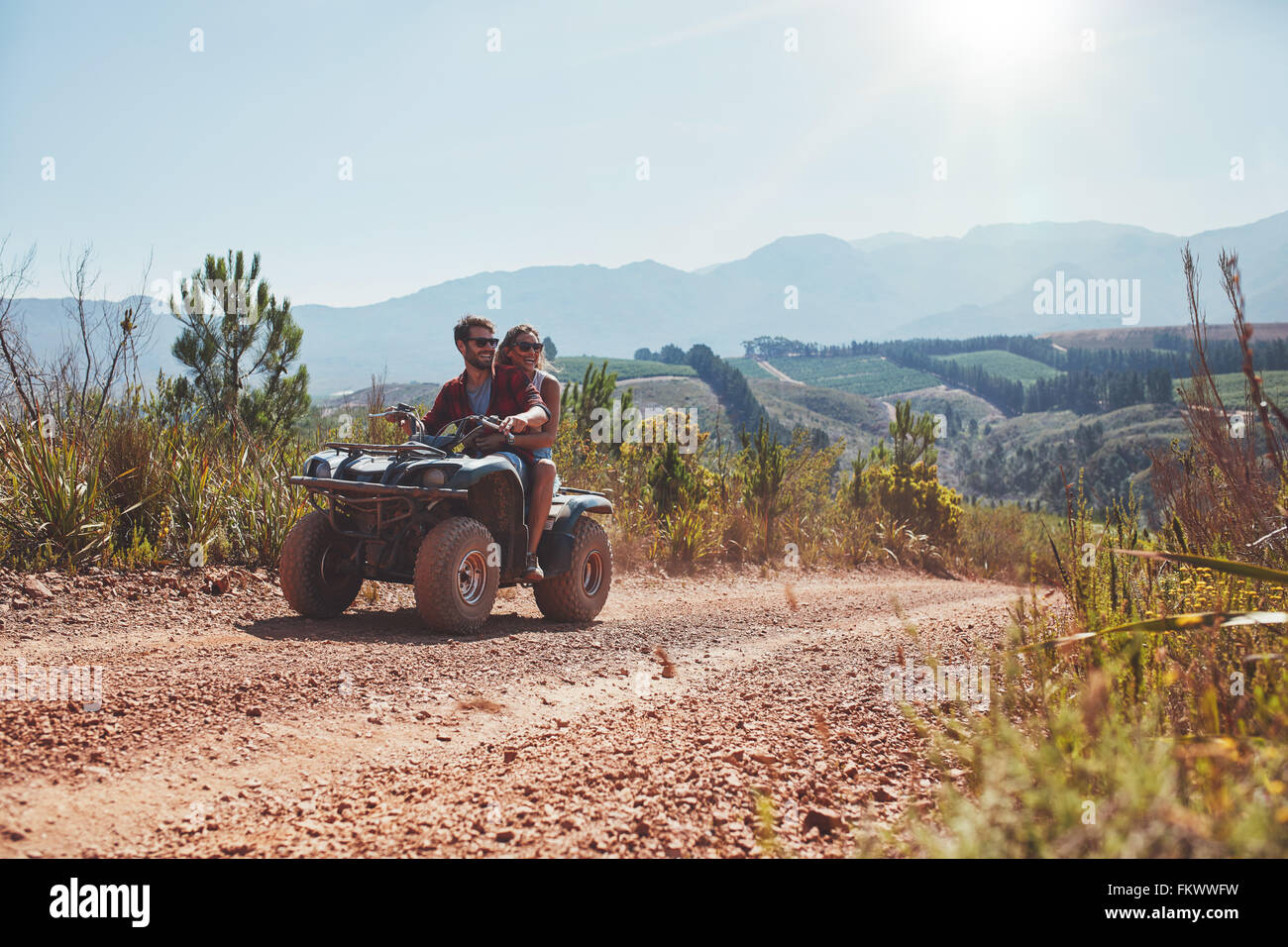 Young man and woman driving a quad bike on country road on a summer day. Couple on holiday enjoying on a ATV bike - Stock Image