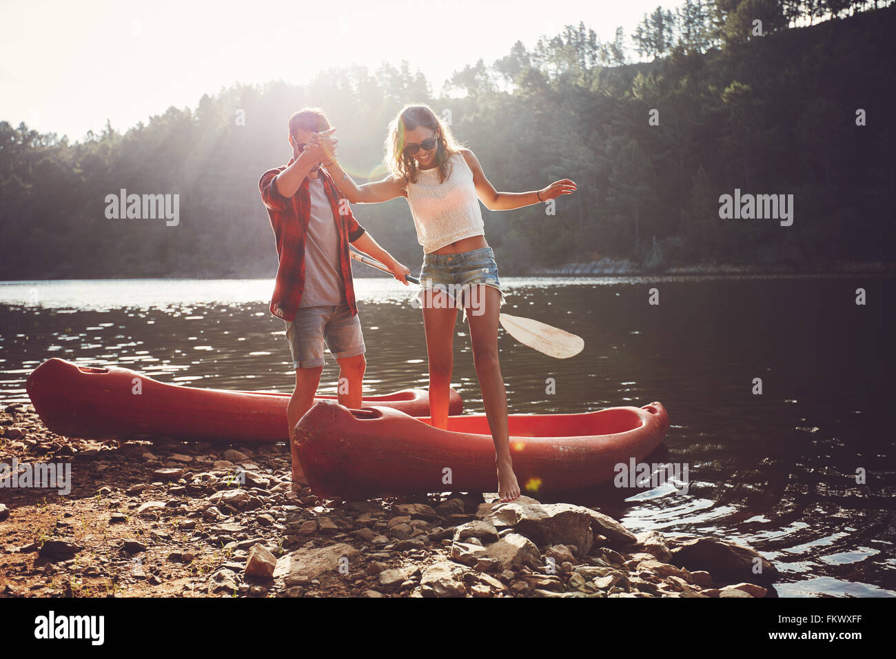 Young man helping woman to step out of canoe. Couple after the canoe ride in the lake. - Stock Image