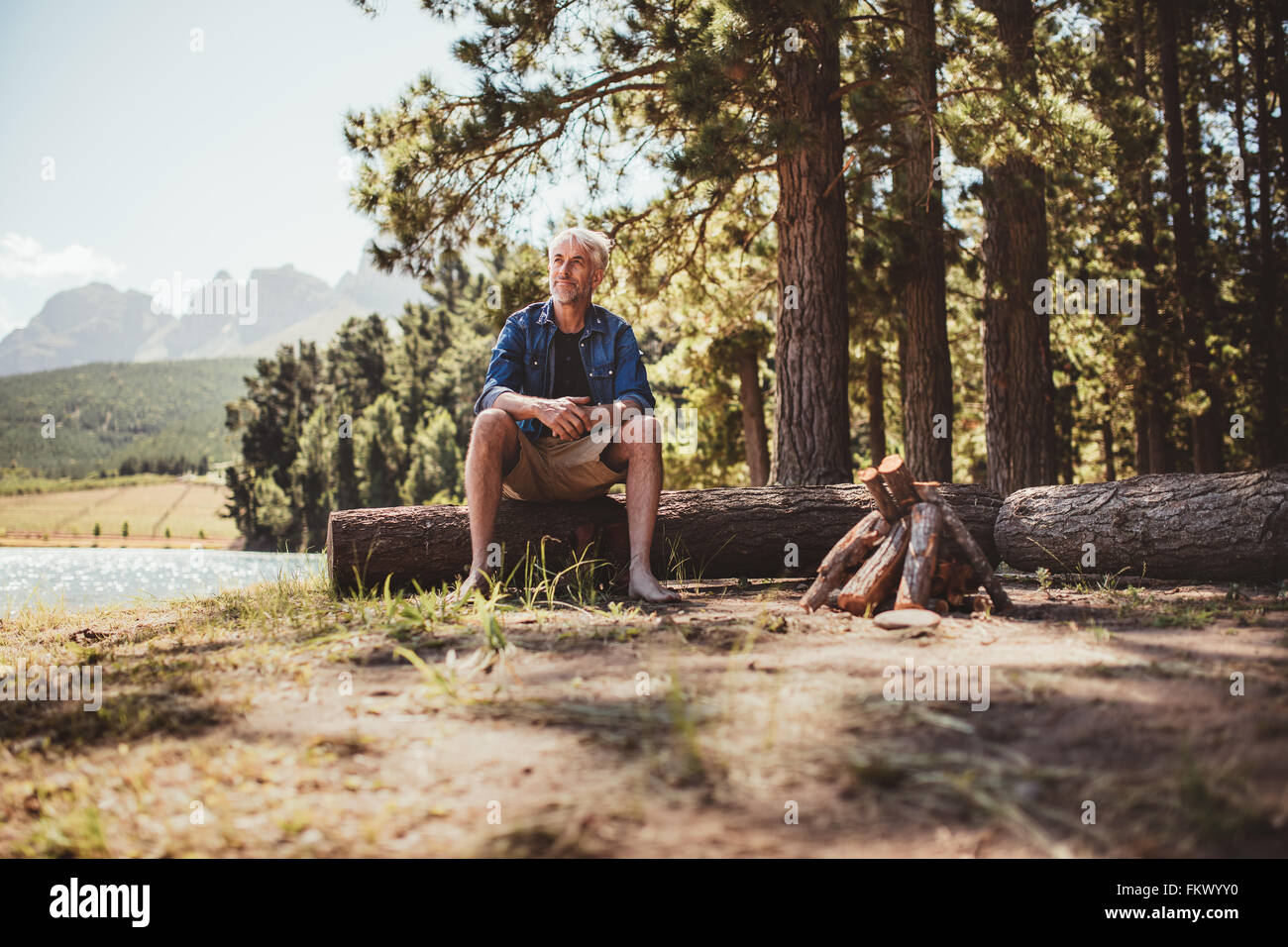 Portrait of a mature man sitting on a log staring out to the lake. Senior man camping by the lake on a summer day. - Stock Image