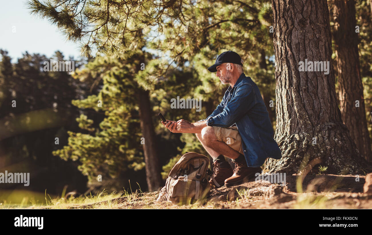 Mature man hiker sitting by a tree in forest and checking his position by using a compass. Senior man on hike in - Stock Image