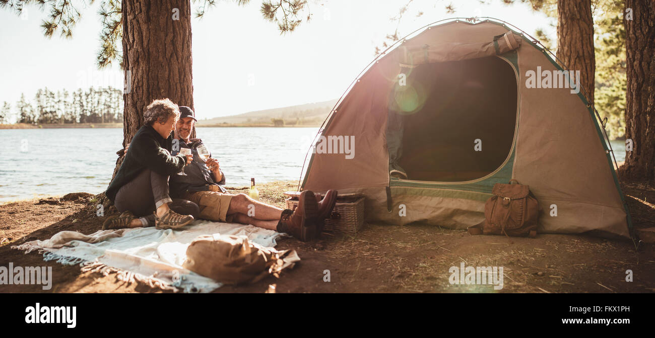 Portrait of mature couple in love camping near a lake. Man and woman sitting outside the tent and drinking wine - Stock Image