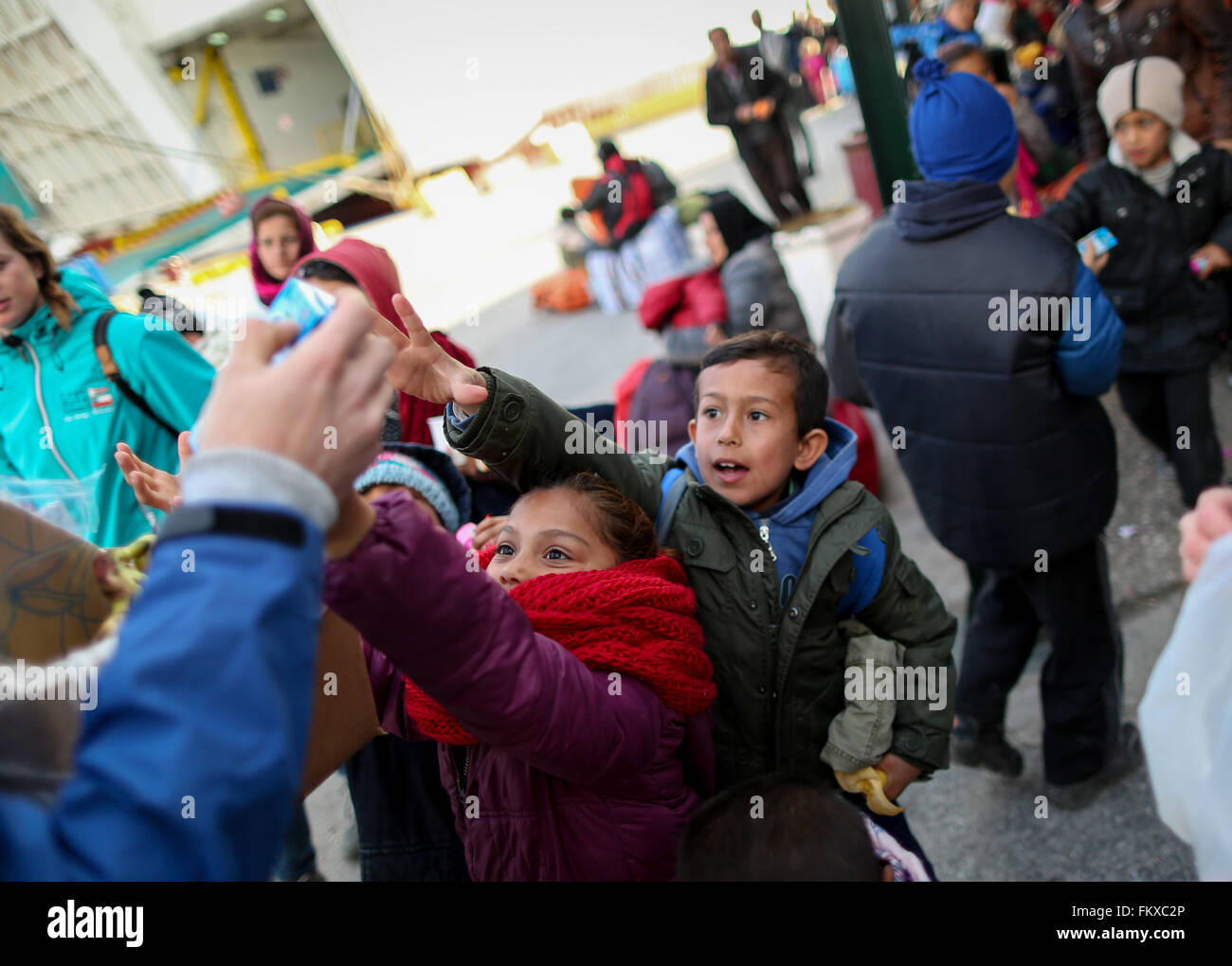 Lesbos, Greece. 10th March, 2016. Refugee children grasp at sweets prior to the departure of a ferry headed to Piraeus, - Stock Image