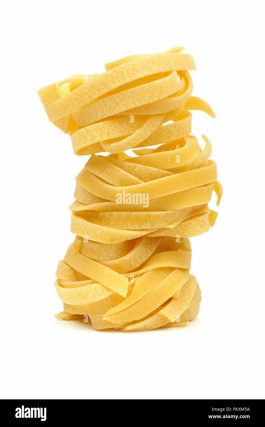 Stack of tagliatelle pasta nests over a white background - Stock Image