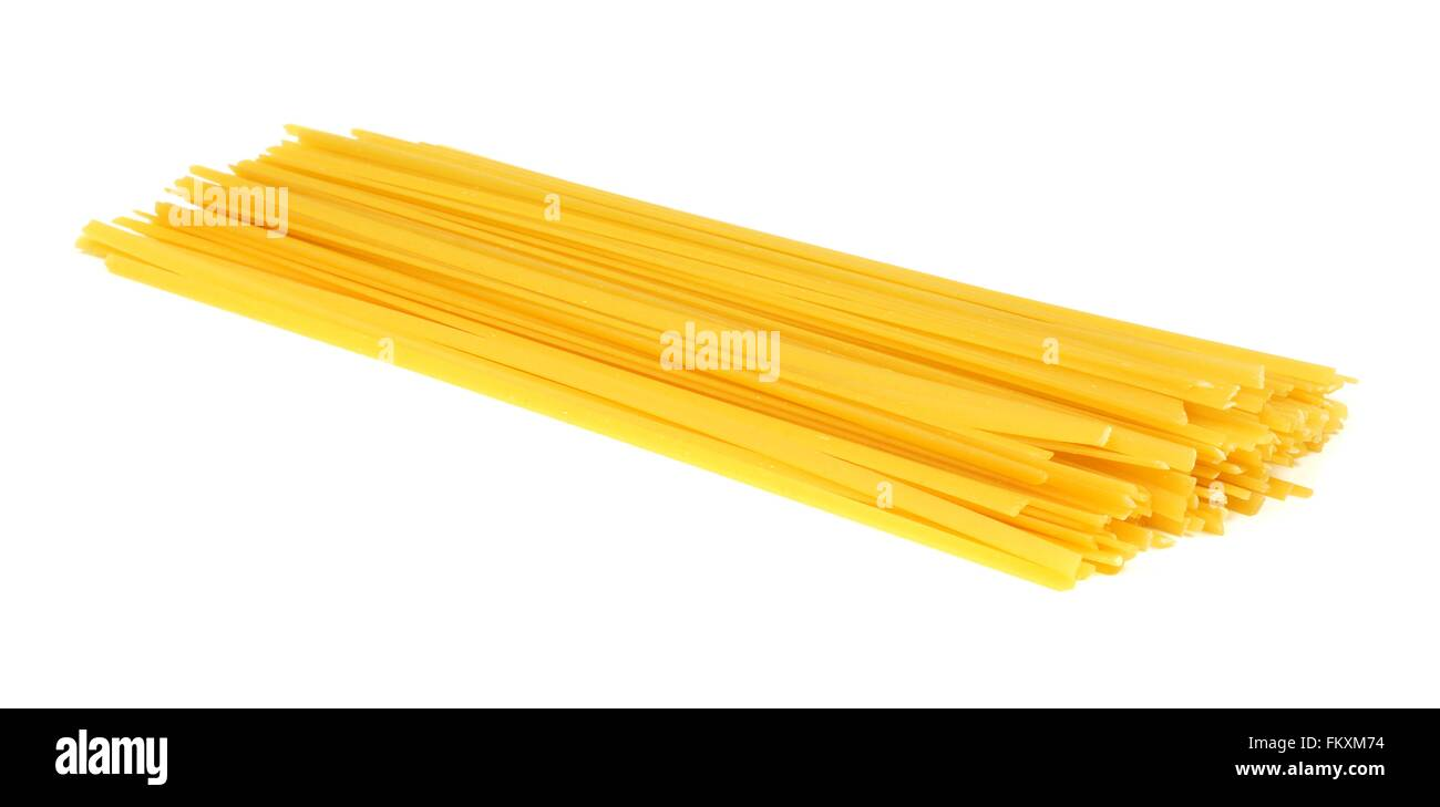 Pile of uncooked dry fettuccine pasta isolated on a white background - Stock Image