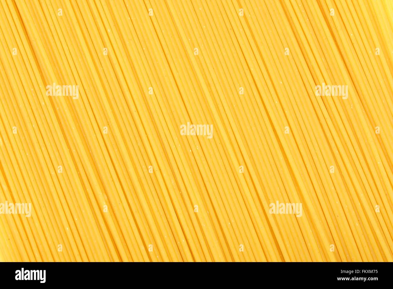 Full background of dry uncooked spaghetti pasta - Stock Image