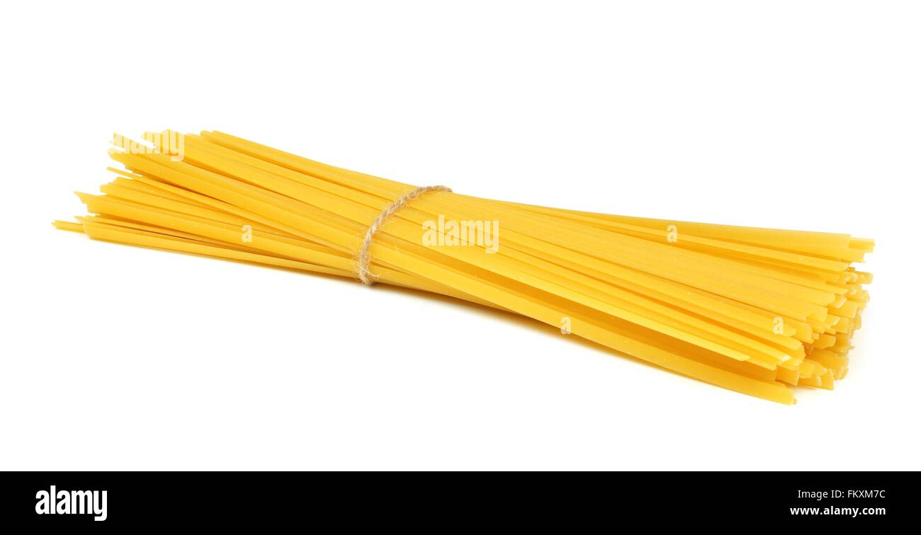 Uncooked dry fettuccine pasta tied in a bundle isolated on a white background - Stock Image