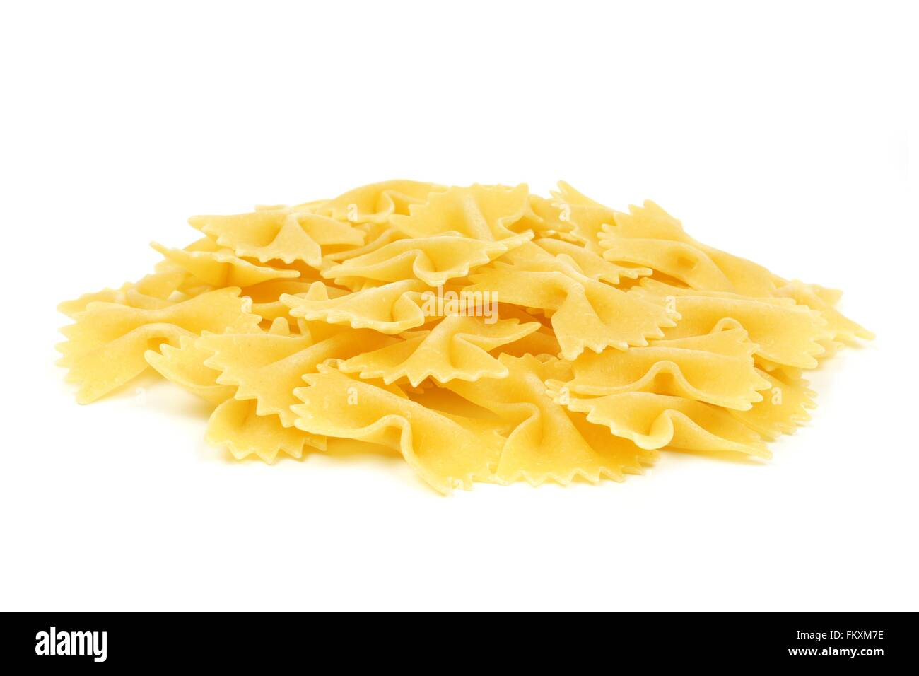 Pile of uncooked dry bow tie pasta isolated on a white background - Stock Image