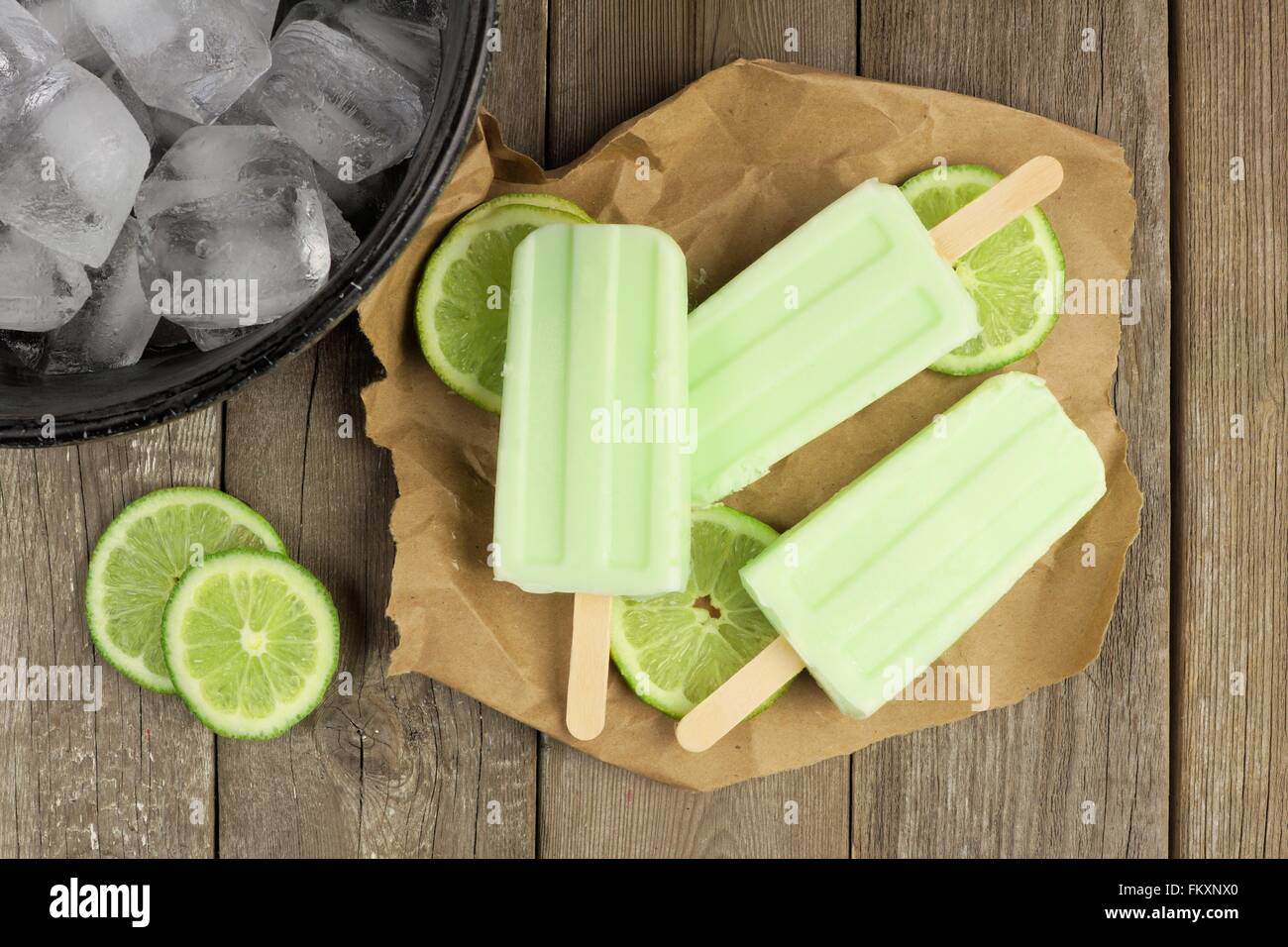 Homemade lime yogurt popsicles with fresh lime slices on paper with rustic wood background - Stock Image