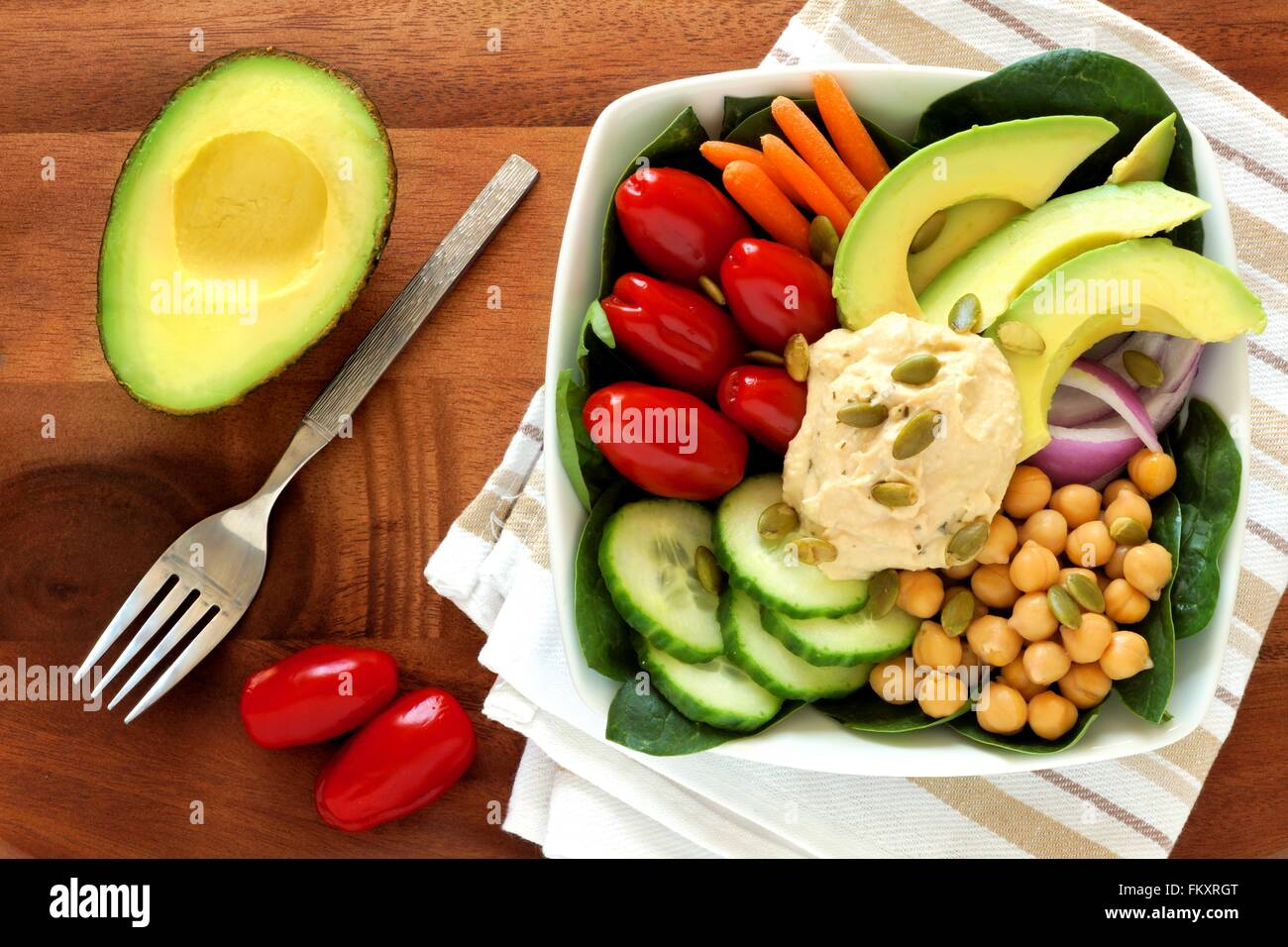 Healthy lunch bowl with avocado, hummus and fresh vegetables, overhead scene on wooden table - Stock Image