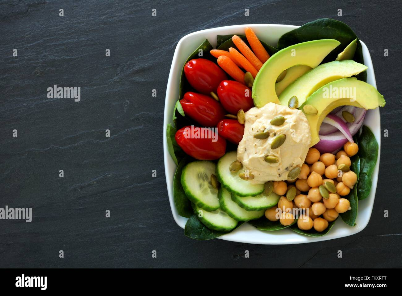 Healthy nourishment bowl with super-foods and fresh mixed vegetables, overhead view on dark slate - Stock Image
