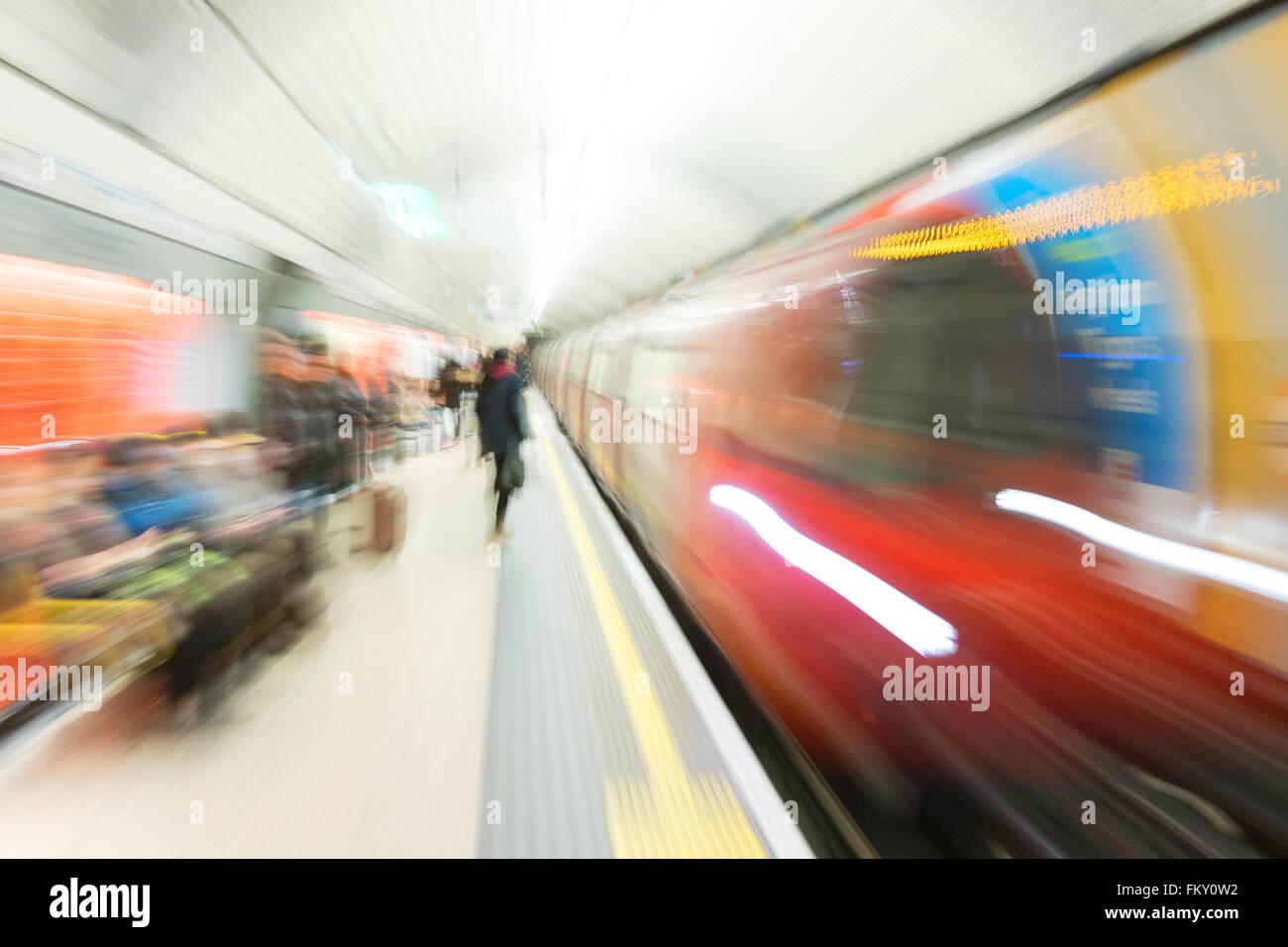 Motion blurred image of a London Underground train arriving at a station platform, Green Park Station, London UK - Stock Image