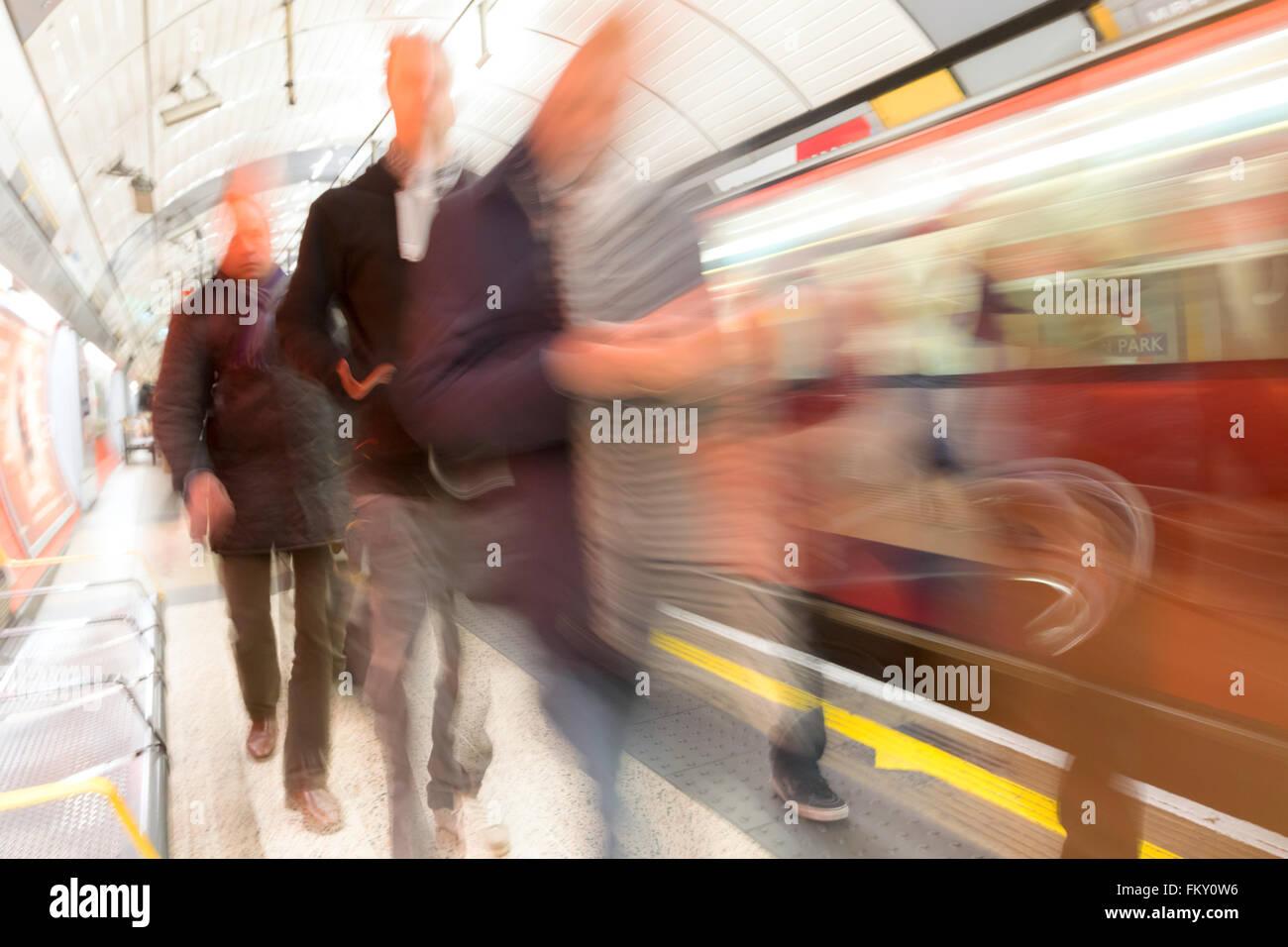London underground train station passengers on the platform, motion blur, Green Park Tube station, London UK - Stock Image