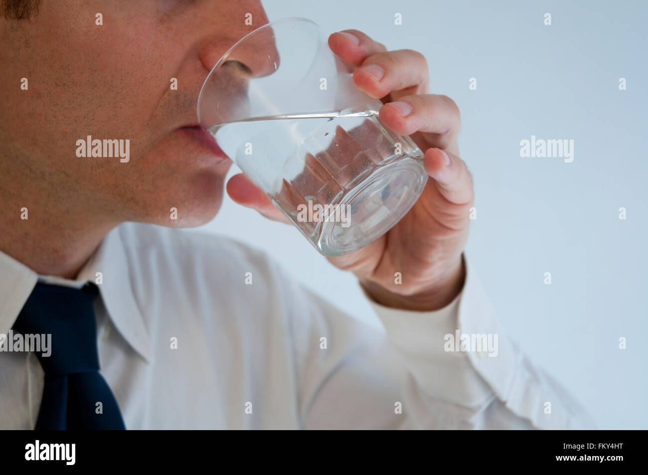 Man drinking a glass of water. Close view. - Stock Image