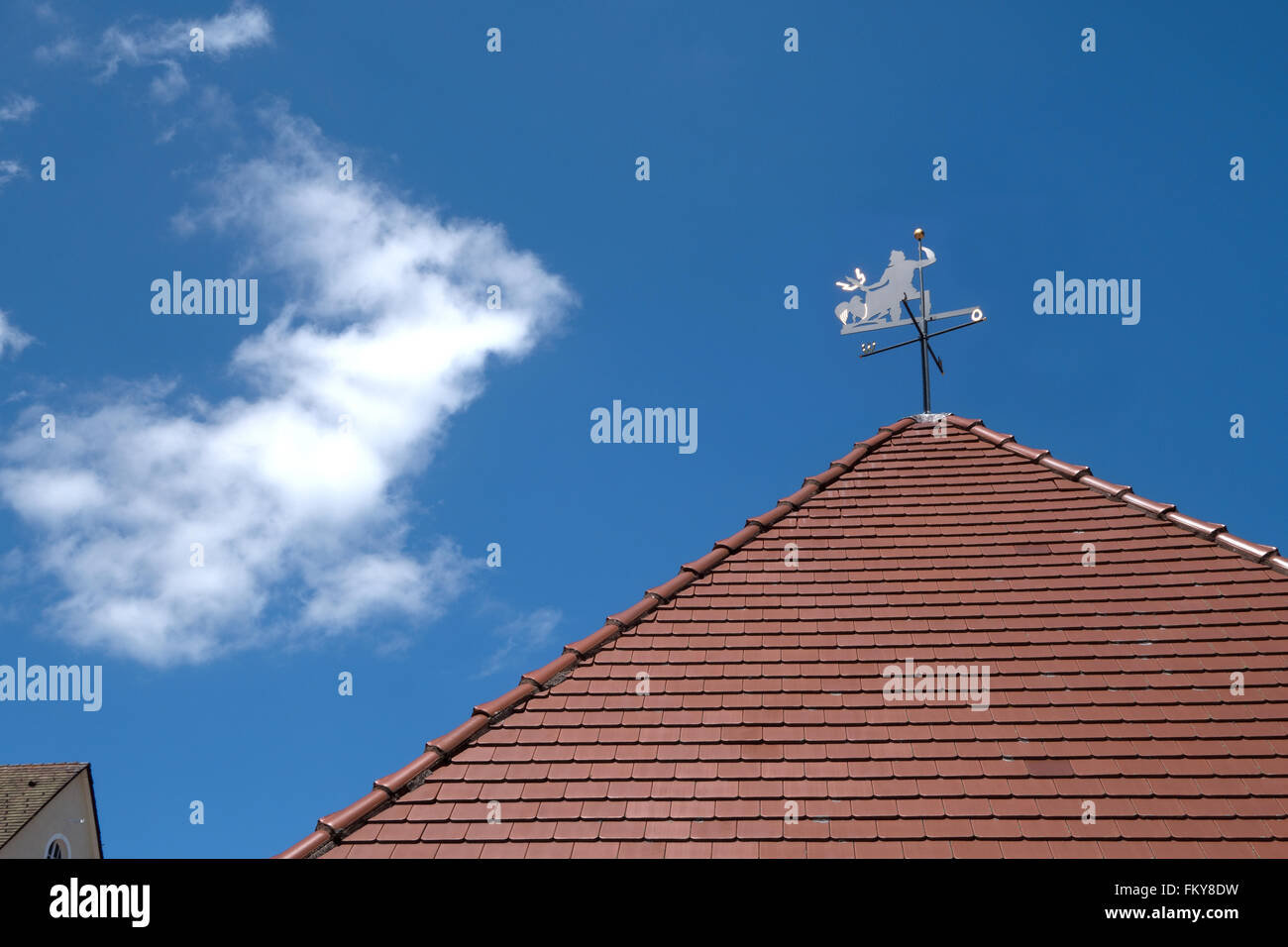 Weather vane with devil and indicator of the compass directions on a pointed roof with red roof tiles against a - Stock Image