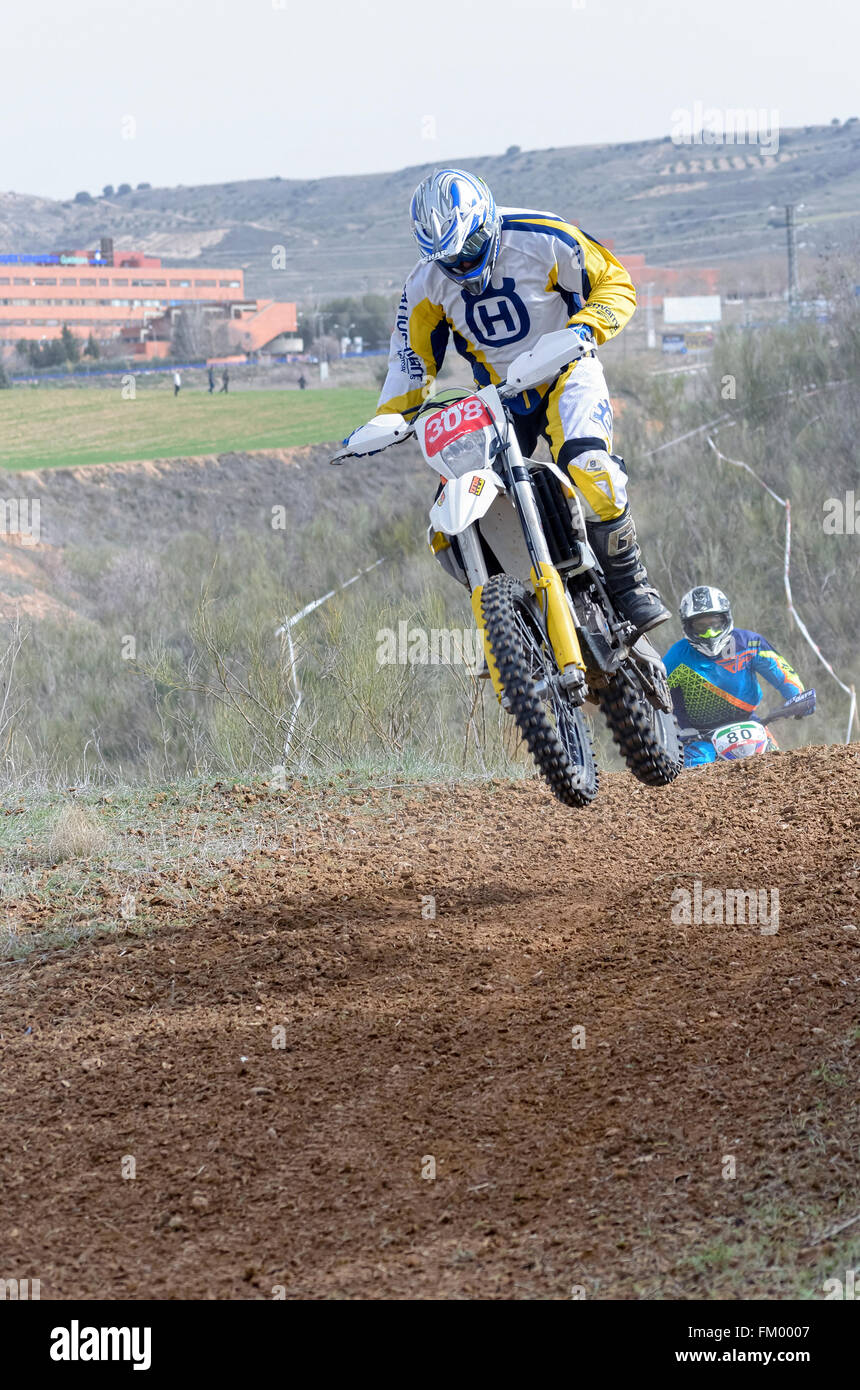 Spain cross country championship. Motorcyclist is jumping with his motocross motorbike, during first race of season - Stock Image